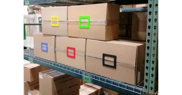 Box Latch - Closing boxes without tape. Large - green, yellow, red, blue, black. Stacked on a shelf.